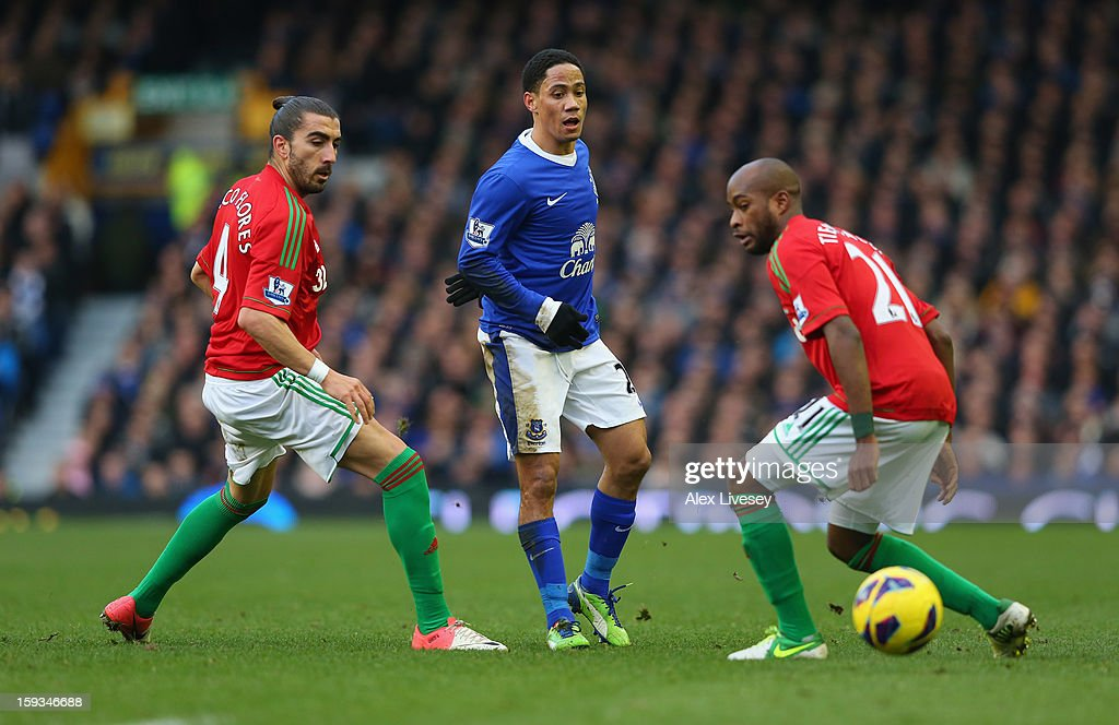 Steven Pienaar of Everton passes the ball between Chico Flores and Dwight Tiendalli of Swansea City during the Barclays Premier League match between Everton and Swansea City at Goodison Park on January 12, 2013 in Liverpool, England.