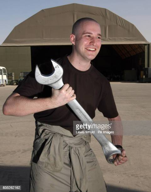 SAC Steven Richardson 24 from Portsmouth laughs as he carries a spanner at Basra airbase in Iraq