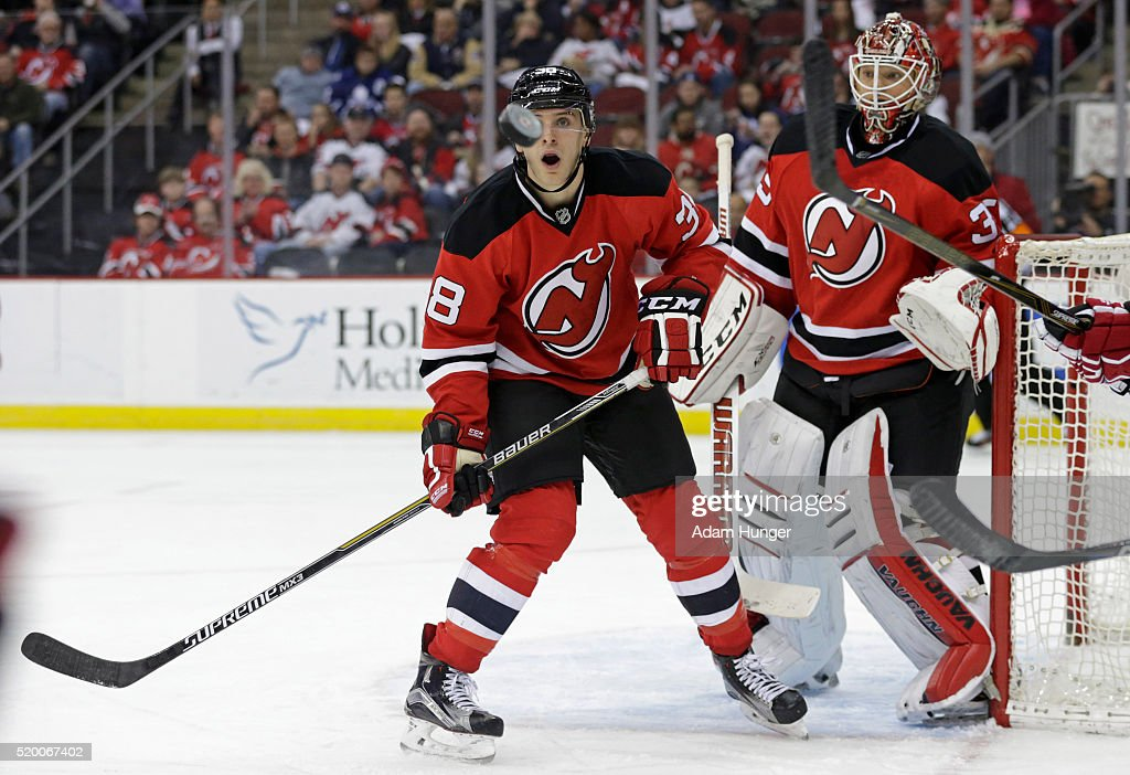 Steven Santini of the New Jersey Devils and Cory Schneider keep their eyes on the puck against the Toronto Maple Leafs during the third period at the...