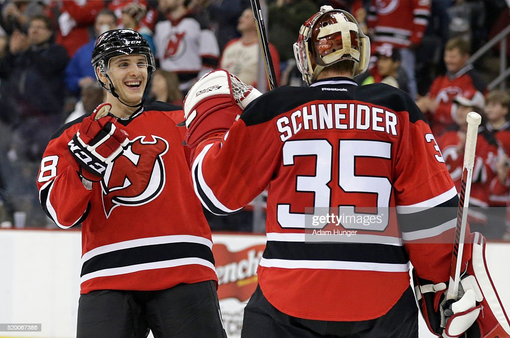 Steven Santini of the New Jersey Devils celebrates with Cory Schneider after defeating the Toronto Maple Leafs at the Prudential Center on April 9...