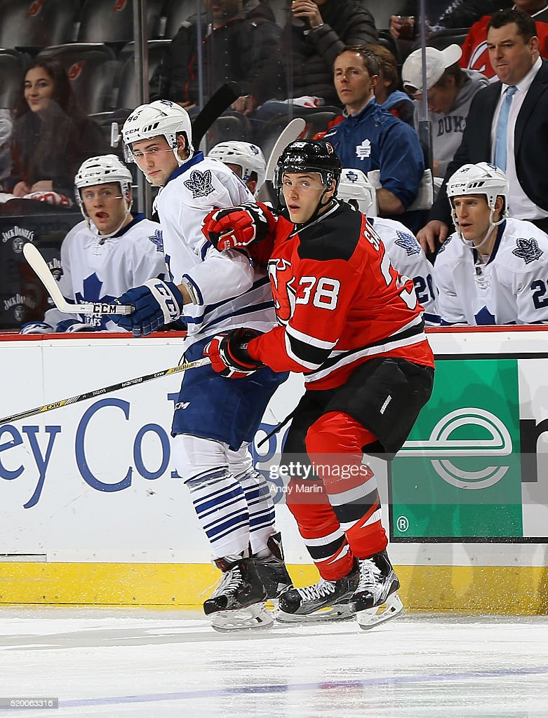 Steven Santini of the New Jersey Devils playing in his first NHL game defends against Tobias Lindberg of the Toronto Maple Leafs during the game at...