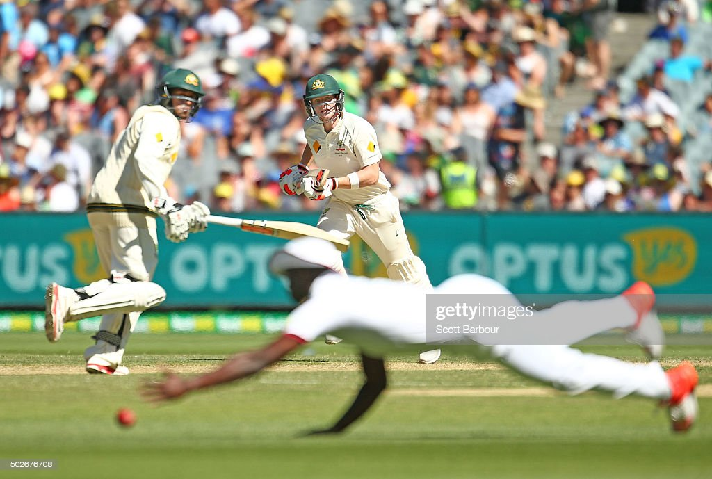 Steven Smith and <a gi-track='captionPersonalityLinkClicked' href=/galleries/search?phrase=Usman+Khawaja&family=editorial&specificpeople=4953179 ng-click='$event.stopPropagation()'>Usman Khawaja</a> of Australia run between the wickets as <a gi-track='captionPersonalityLinkClicked' href=/galleries/search?phrase=Kemar+Roach&family=editorial&specificpeople=5408487 ng-click='$event.stopPropagation()'>Kemar Roach</a> of the West Indies dives for the ball during day three of the Second Test match between Australia and the West Indies at the Melbourne Cricket Ground on December 28, 2015 in Melbourne, Australia.