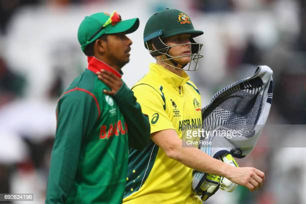 Steven Smith of Australia leaves the field with his bat wrapped in a towel to protect it from the falling rain as play is suspended during the ICC...