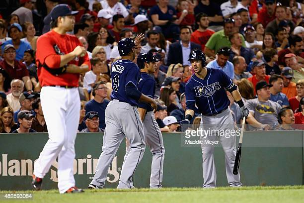 Steven Souza Jr #20 of the Tampa Bay Rays congratulates Joey Butler and Mikie Mahtook after they scored runs against the Boston Red Sox during the...