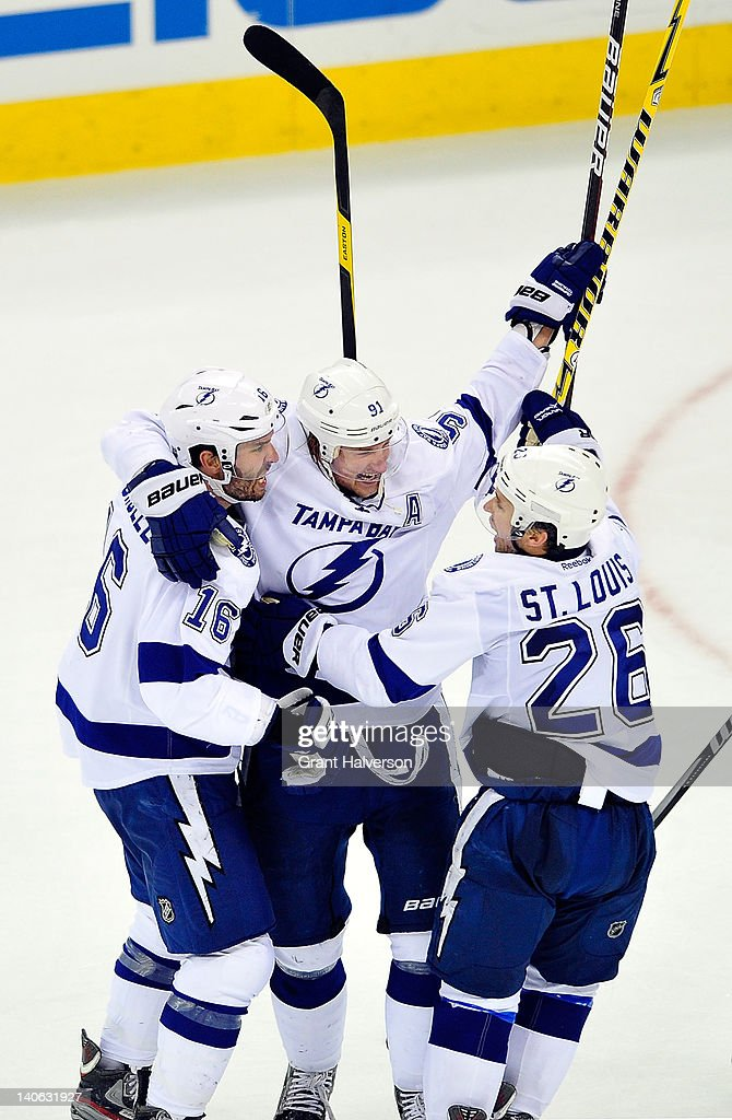 <a gi-track='captionPersonalityLinkClicked' href=/galleries/search?phrase=Steven+Stamkos&family=editorial&specificpeople=4047623 ng-click='$event.stopPropagation()'>Steven Stamkos</a> #91 celebrates with teammate <a gi-track='captionPersonalityLinkClicked' href=/galleries/search?phrase=Teddy+Purcell&family=editorial&specificpeople=4537302 ng-click='$event.stopPropagation()'>Teddy Purcell</a> #16 and <a gi-track='captionPersonalityLinkClicked' href=/galleries/search?phrase=Martin+St.+Louis&family=editorial&specificpeople=202067 ng-click='$event.stopPropagation()'>Martin St. Louis</a> #26 of the Tampa Bay Lightning after scoring the game-winning goal against the Carolina Hurricanes during overtime at the RBC Center on March 3, 2012 in Raleigh, North Carolina. The Lightning won 4-3 in overtime.
