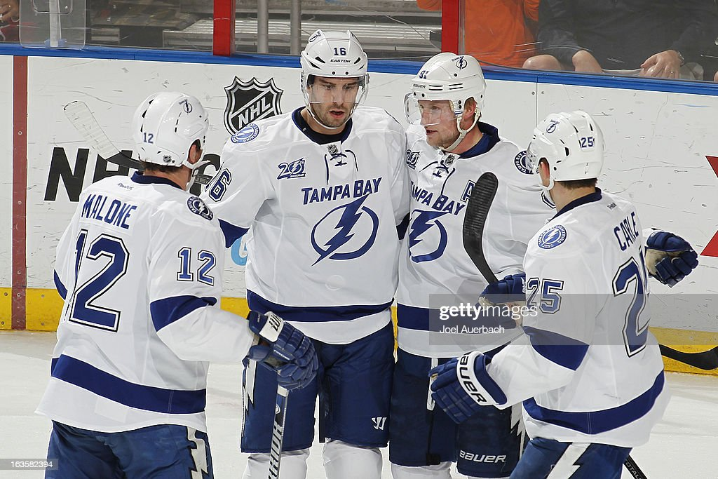 Steven Stamkos #91 is congratulated by Ryan Malone #12, Teddy Purcell #16, and Matt Carle #25 of the Tampa Bay Lightning after scoring the game-winning goal against the Florida Panthers in the third period at the BB&T Center on March 12, 2013 in Sunrise, Florida. The Lightning defeated the Panthers 3-2.