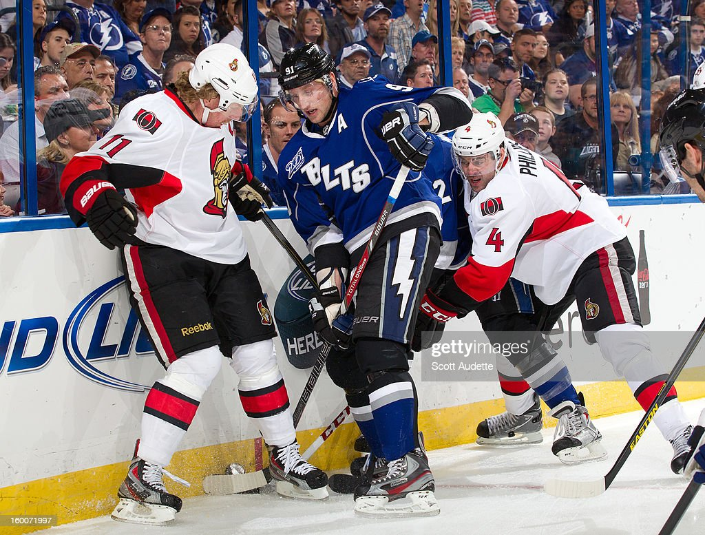 <a gi-track='captionPersonalityLinkClicked' href=/galleries/search?phrase=Steven+Stamkos&family=editorial&specificpeople=4047623 ng-click='$event.stopPropagation()'>Steven Stamkos</a> #91 of the Tampa Bay Lightning battles for the puck against <a gi-track='captionPersonalityLinkClicked' href=/galleries/search?phrase=Daniel+Alfredsson&family=editorial&specificpeople=201853 ng-click='$event.stopPropagation()'>Daniel Alfredsson</a> #11 and Chris Phillips #4 of the Ottawa Senators during the first period at the Tampa Bay Times Forum on January 25, 2013 in Tampa, Florida.