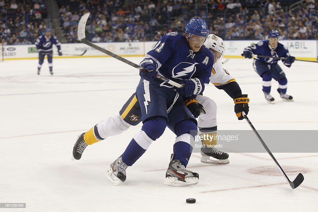 Steven Stamkos #91 of the Tampa Bay Lightning battles to keep control of the puck against Kevin Klein #8 of the Nashville Predators at Tampa Bay Times Forum on September 19, 2013 in Tampa, Florida.