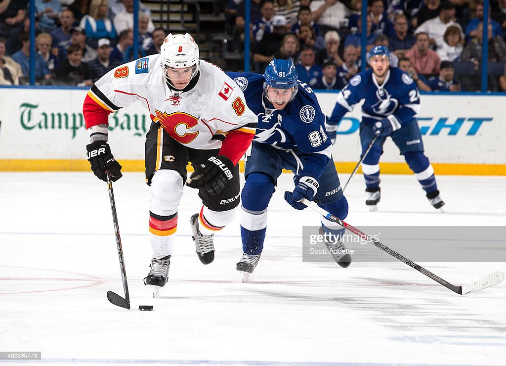 Steven Stamkos #91 of the Tampa Bay Lightning chases Joe Colborne #8 of the Calgary Flames during the second period at the Tampa Bay Times Forum on April 3, 2014 in Tampa, Florida.