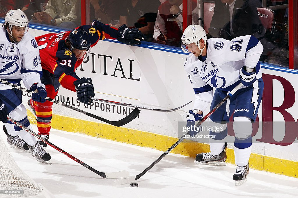 Steven Stamkos #91 of the Tampa Bay Lightning digs the puck out from the boards with teammate Cory Conacher #89 against Brian Campbell #51 of the Florida Panthers at the BB&T Center on February 16, 2013 in Sunrise, Florida.