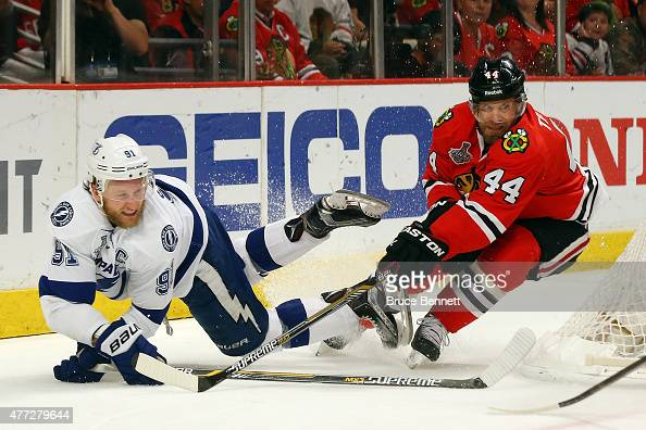 Steven Stamkos of the Tampa Bay Lightning falls to the ice as he takes a shot on Corey Crawford of the Chicago Blackhawks while being defended by...
