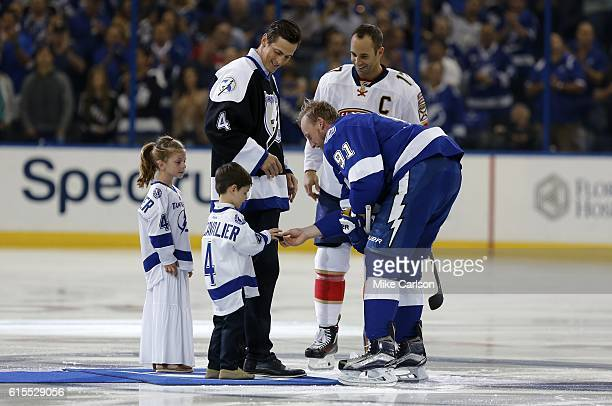Steven Stamkos of the Tampa Bay Lightning hands the ceremonial face off puck to Gabriel Lecavalier as his father Vincent Lecavalier sister Victoria...