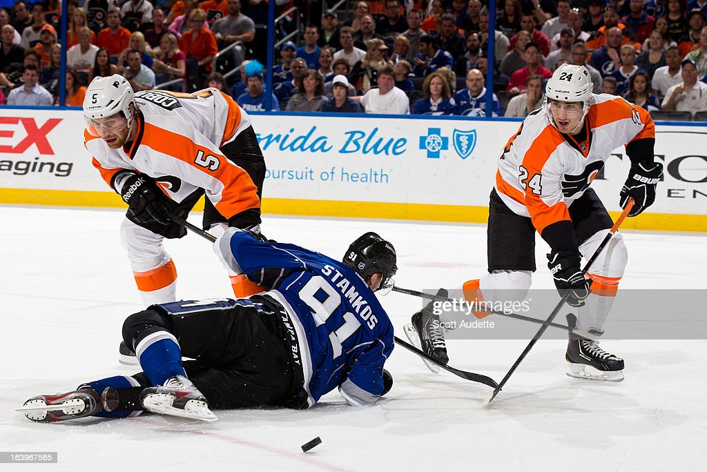 Steven Stamkos #91 of the Tampa Bay Lightning hits the ground while fighting for possession of the puck with Braydon Coburn #5 of the Philadelphia Flyers and Matt Read #24 during the first period of the game at the Tampa Bay Times Forum on March 18, 2013 in Tampa, Florida.