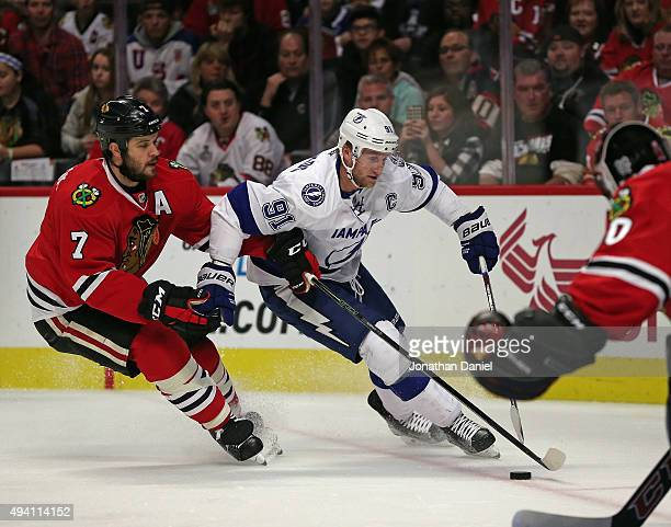 Steven Stamkos of the Tampa Bay Lightning is pressured by Brent Seabrook of the Chicago Blackhawks as he skates toward Corey Crawford at the United...