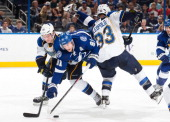 Steven Stamkos of the Tampa Bay Lightning is sandwiched between Jordan Leopold and Vladimir Tarasenko of the St Louis Blues during the third period...
