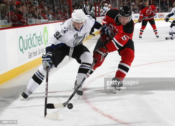 Steven Stamkos of the Tampa Bay Lightning moves around Colin White of the New Jersey Devils at the Prudential Center on December 4 2009 in Newark New...