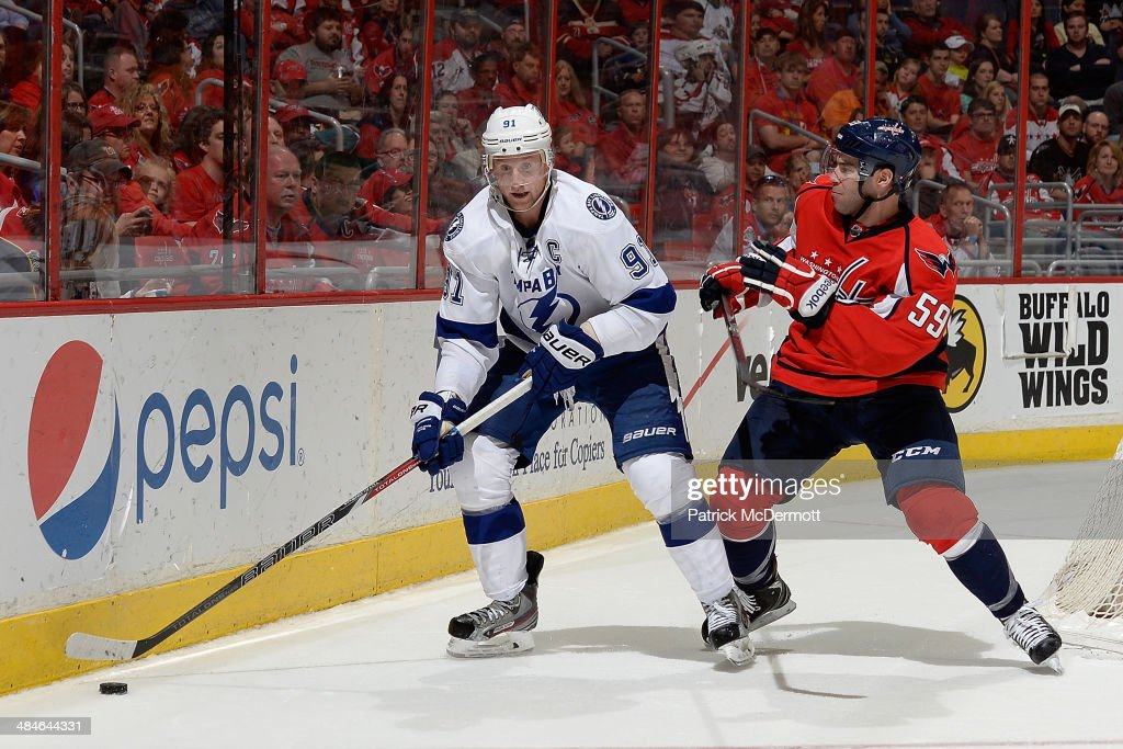 Steven Stamkos #91 of the Tampa Bay Lightning moves the puck against Julien Brouillette #59 of the Washington Capitals in the third period during an NHL game at Verizon Center on April 13, 2014 in Washington, DC.