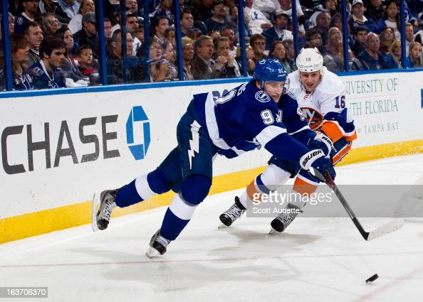 Steven Stamkos of the Tampa Bay Lightning reaches for the puck over Marty Reasoner of the New York Islanders during the third period of the game at...
