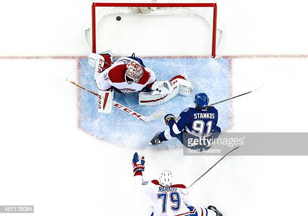 Steven Stamkos of the Tampa Bay Lightning shoots the puck through the legs of goalie Carey Price of the Montreal Canadiens for a goal after out...