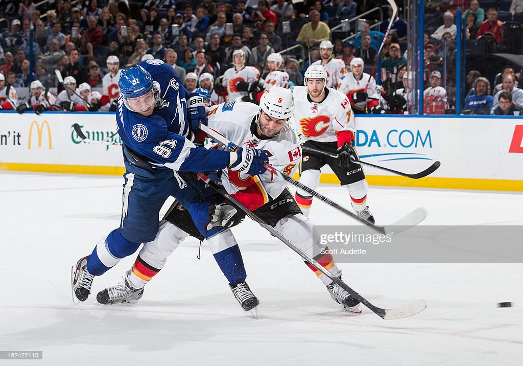 <a gi-track='captionPersonalityLinkClicked' href=/galleries/search?phrase=Steven+Stamkos&family=editorial&specificpeople=4047623 ng-click='$event.stopPropagation()'>Steven Stamkos</a> #91 of the Tampa Bay Lightning shoots the puck while being hit by <a gi-track='captionPersonalityLinkClicked' href=/galleries/search?phrase=Mark+Giordano&family=editorial&specificpeople=696867 ng-click='$event.stopPropagation()'>Mark Giordano</a> #5 of the Calgary Flames during the third period at the Tampa Bay Times Forum on April 3, 2014 in Tampa, Florida.
