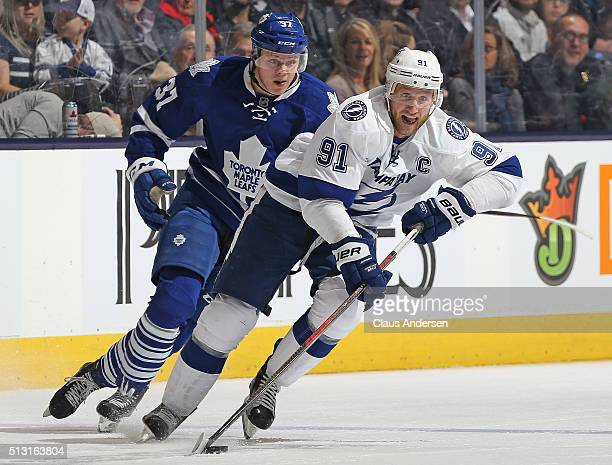Steven Stamkos of the Tampa Bay Lightning skates away from a checking Kasperi Kapanen of the Toronto Maple Leafs during an NHL game at the Air Canada...