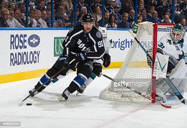 Steven Stamkos of the Tampa Bay Lightning skates the puck behind the net against goalie Antti Niemi and Tomas Hertl of the San Jose Sharks during the...