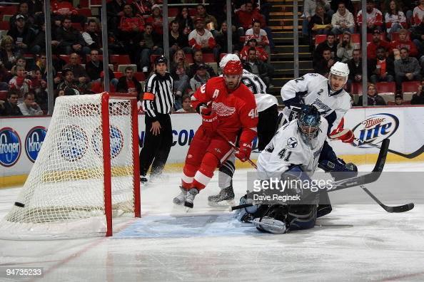 Steven Stamkos of the Tampa Bay Lightning teammate Lukas Krajicek and Mike Smith watch the puck as Henrik Zetterberg of the Detroit Red Wings skates...