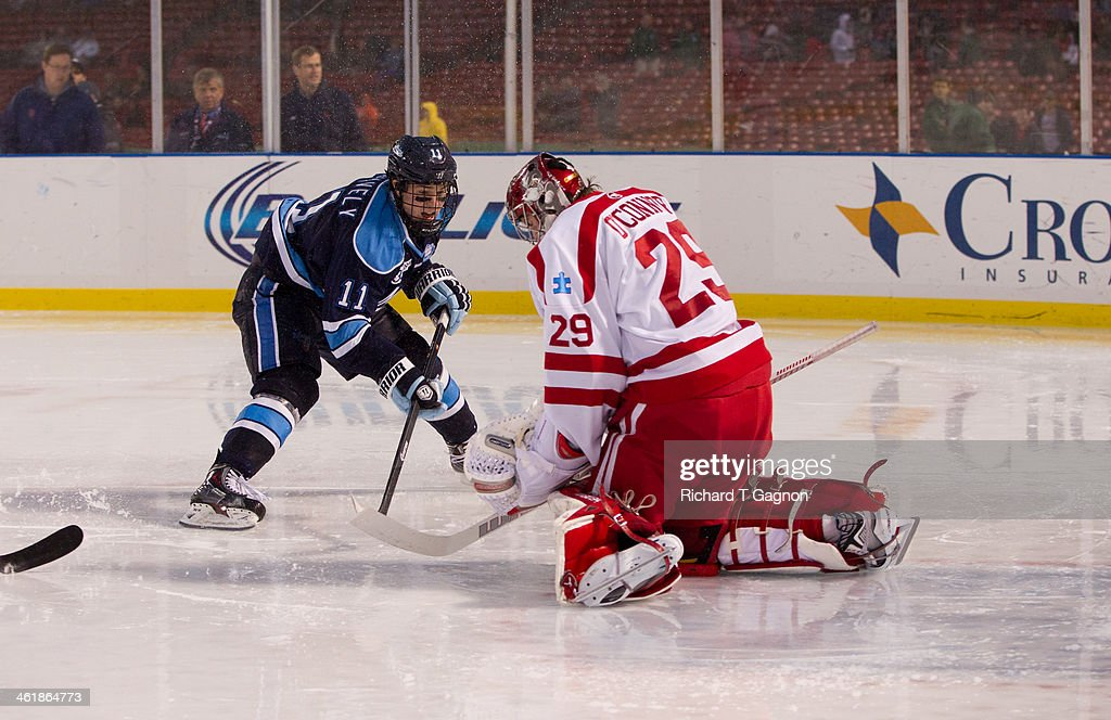 Steven Swavely #11 of the Maine Black Bears takes a shot on Matt O'Connor #29 of the Boston University Terriers during NCAA hockey action in the 'Citi Frozen Fenway 2014' at Fenway Park on January 11, 2014 in Boston, Massachusetts.