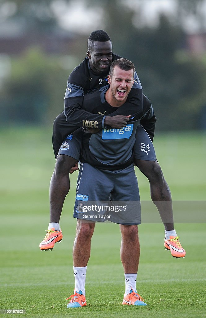 Steven Taylor (bottom) laughs as Cheick Tiote jumps on his back during a training session at The Newcastle United Training Centre on September 27, 2014, in Newcastle upon Tyne, England.