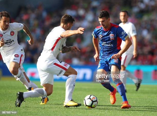 Steven Ugarkovic of the Jets contests the ball with Alvaro Cejudo of the Wanderers during the round four ALeague match between the Newcastle Jets and...
