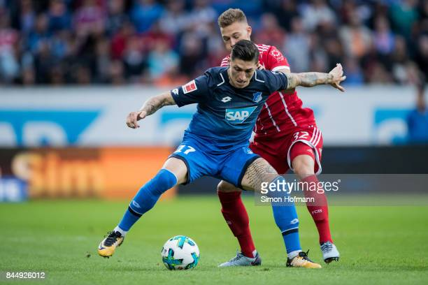 Steven Zuber of Hoffenheim is challenged by Joshua Kimmich of Muenchen during the Bundesliga match between TSG 1899 Hoffenheim and FC Bayern Muenchen...