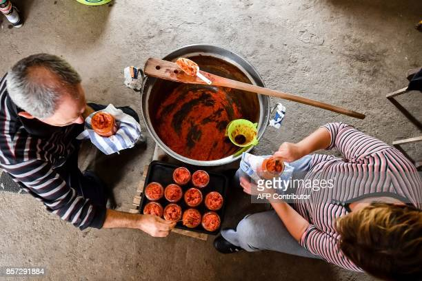 BRIEN Stevica Markovic and his wife Suncica fill a jars with 'ajvar' in their kitchen in Brestovac village near the south Serbian town of Leskovac on...