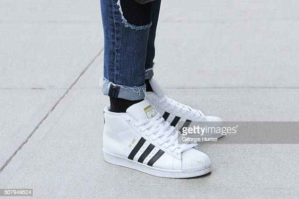 Stevie Gatez seen at Industria Superstudios wearing black and white Adidas sneakers and ripped Topman denim jeans during New York Fashion Week Men's...