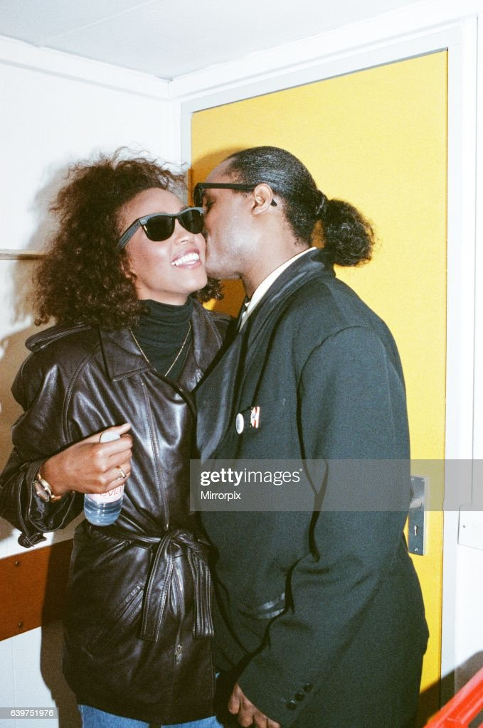 Stevie Wonder kisses Whitney Houston on the cheek as they laugh backstage at the Nelson Mandela Concert in London on 11th June 1988.