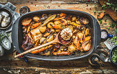 Stew with roasted vegetables, forest mushrooms and wild hunting fowl in cooking pot with wooden spoon. Rabbit ragout on rustic aged background with spoons,plates and fresh seasoning, top view