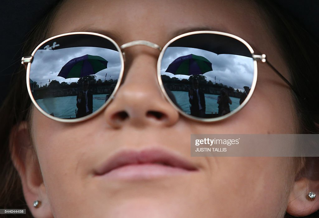 A steward holding an umbrella is reflected in the sunglasses of a spectator as rain stops play on the fifth day of the 2016 Wimbledon Championships at The All England Lawn Tennis Club in Wimbledon, southwest London, on July 1, 2016. / AFP / JUSTIN