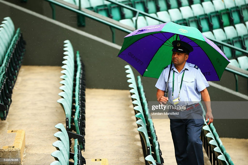 A steward looks on from underneith his umbrella on day three of the Wimbledon Lawn Tennis Championships at the All England Lawn Tennis and Croquet Club on June 29, 2016 in London, England.