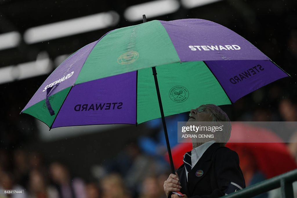 A steward looks up into her umbrella after rain stopped play on the second day of the 2016 Wimbledon Championships at The All England Lawn Tennis Club in Wimbledon, southwest London, on June 28, 2016. / AFP / ADRIAN
