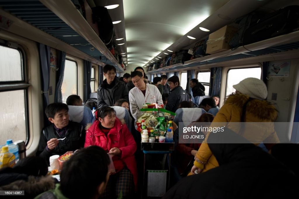 A steward offers snacks from a trolley to Lunar New Year travellers aboard a crowded train bound for the southwestern Chinese city of Chongqing, a journey of 32 hours, after departing from the West Railway Station in Beijing on January 31, 2013. The world's largest annual migration is underway in China with tens of millions across China boarding trains to journey home for Lunar New Year celebrations. Passengers will log 220 million train rides during the 40-day travel season as they criss-cross the country to celebrate with their families on February 10, but just as making the trip home can be laborious -- often lasting one or two days -- so can simply acquiring a seat on the train, and every year complaints arise about the inefficiency or unfairness of the system, although an initiative allowing travelers to purchase tickets online aims to curb long queuing times. AFP PHOTO / Ed Jones