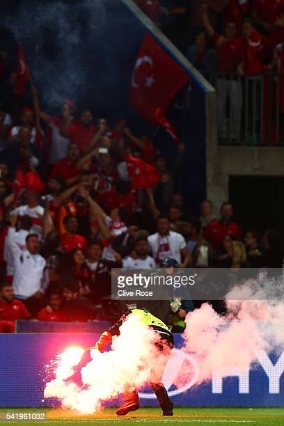 A steward removes a flare during the UEFA EURO 2016 Group D match between Czech Republic and Turkey at Stade BollaertDelelis on June 21 2016 in Lens...
