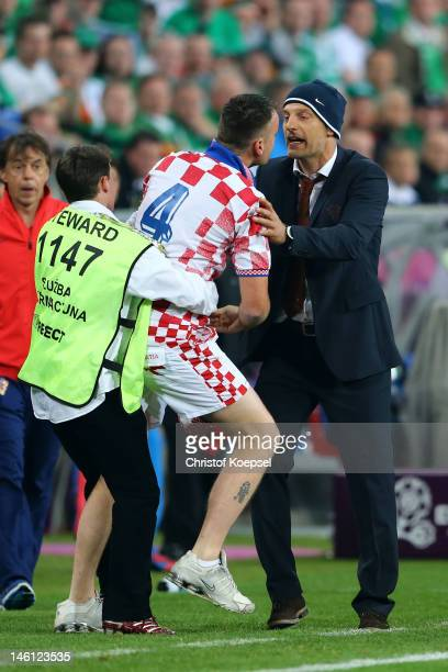 A steward restrains a pitch invader as he tries to speak to Head Coach Slaven Bilic of Croatia during the UEFA EURO 2012 group C between Ireland and...