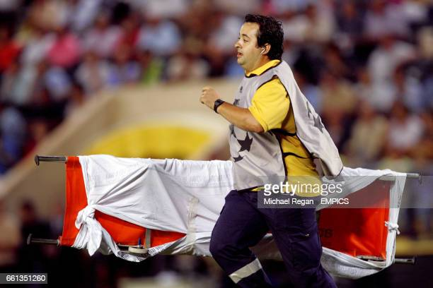 A steward runs on with a stretcher