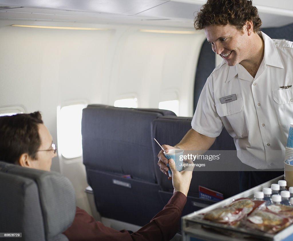 Steward serving passenger on airplane