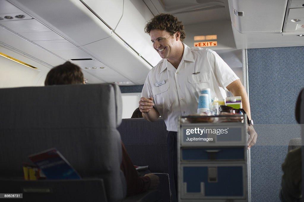 Steward serving passengers on airplane