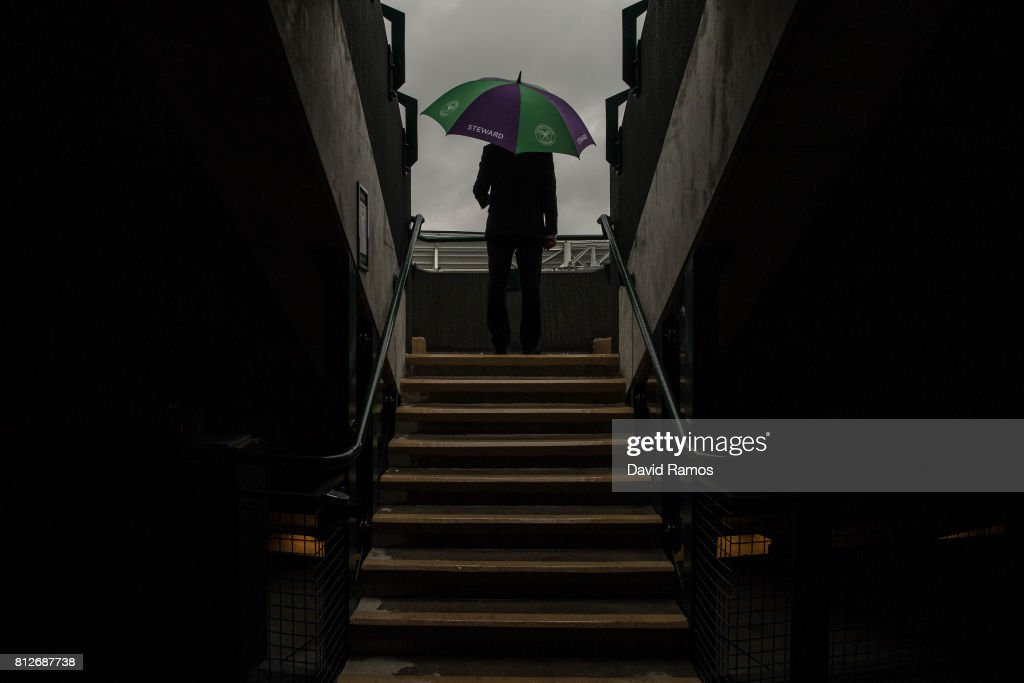 A steward shelters from the rain at court 1 on day eight of the Wimbledon Lawn Tennis Championships at the All England Lawn Tennis and Croquet Club on July 11, 2017 in London, England.