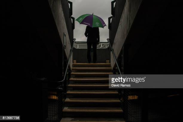 A steward shelters from the rain at court 1 on day eight of the Wimbledon Lawn Tennis Championships at the All England Lawn Tennis and Croquet Club...