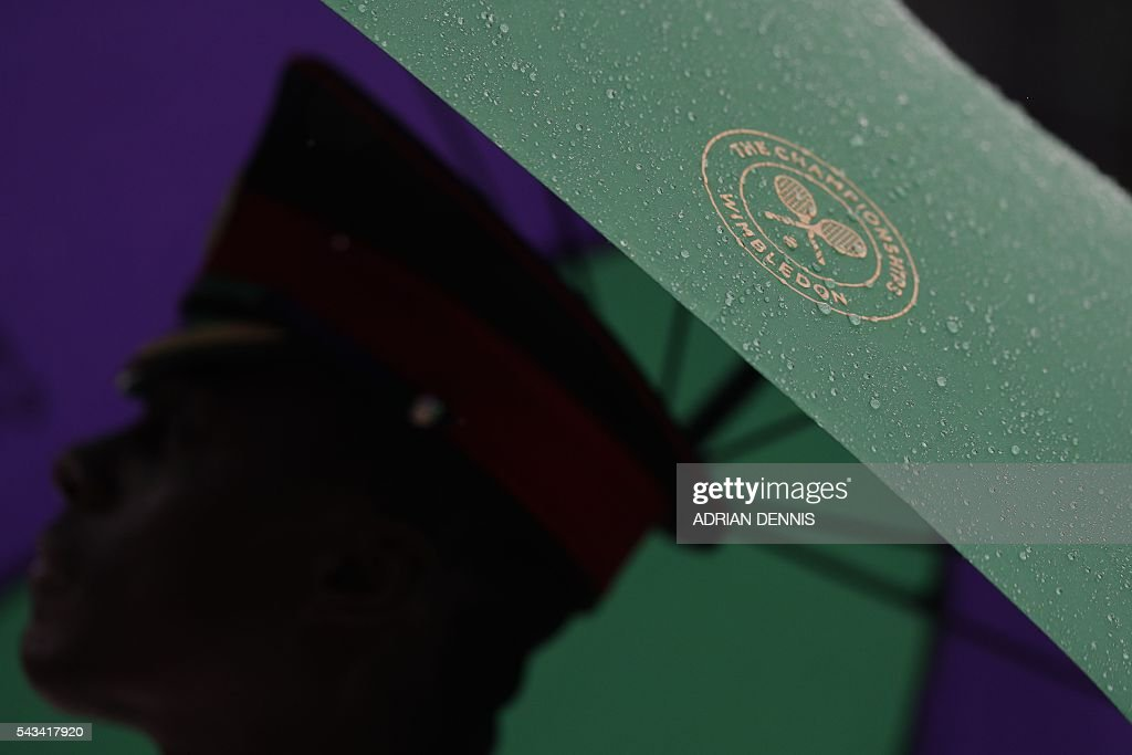 A steward shelters under an umbrella after rain stopped play on the second day of the 2016 Wimbledon Championships at The All England Lawn Tennis Club in Wimbledon, southwest London, on June 28, 2016. / AFP / ADRIAN