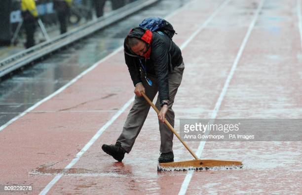 A steward sweeps water from the track as rain falls during the Great City Games Manchester