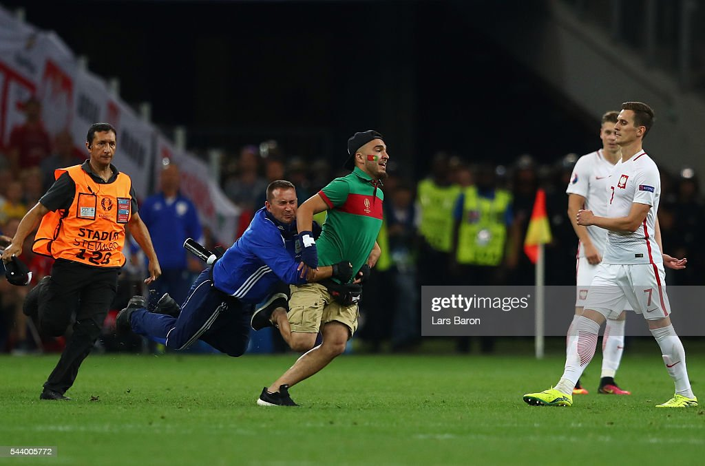A steward tackles an invading fan during the UEFA EURO 2016 quarter final match between Poland and Portugal at Stade Velodrome on June 30, 2016 in Marseille, France.