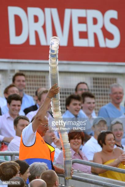 A steward takes away a 'cup snake' made form the empty plastic beer glasses